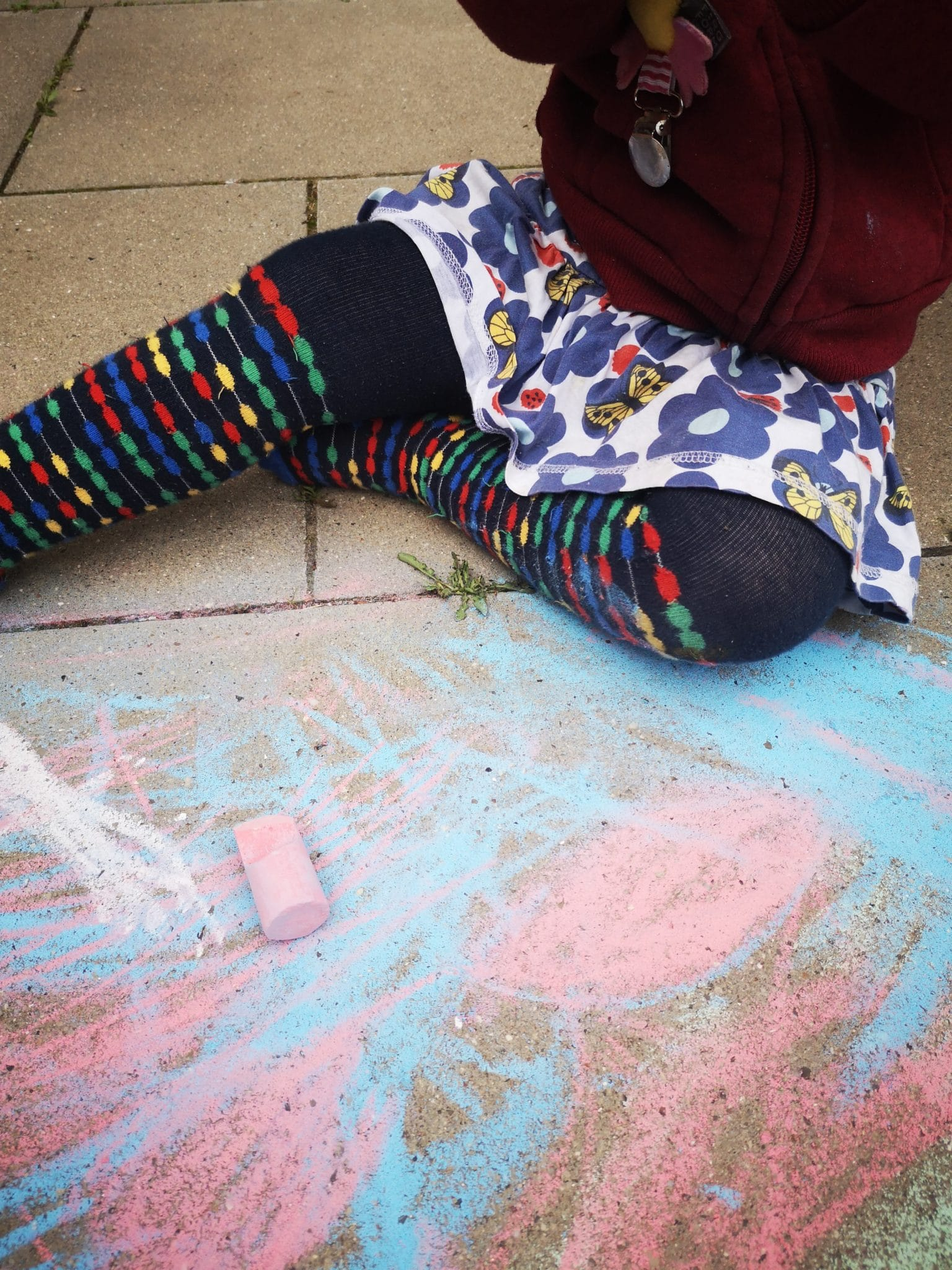 Kind mal mit Kreide auf den Boden.