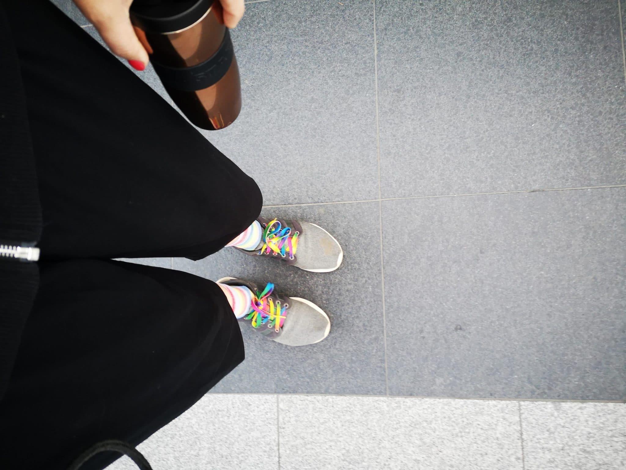 Frau mit Kaffee in der Hand und Regenbogenschnürsenkeln