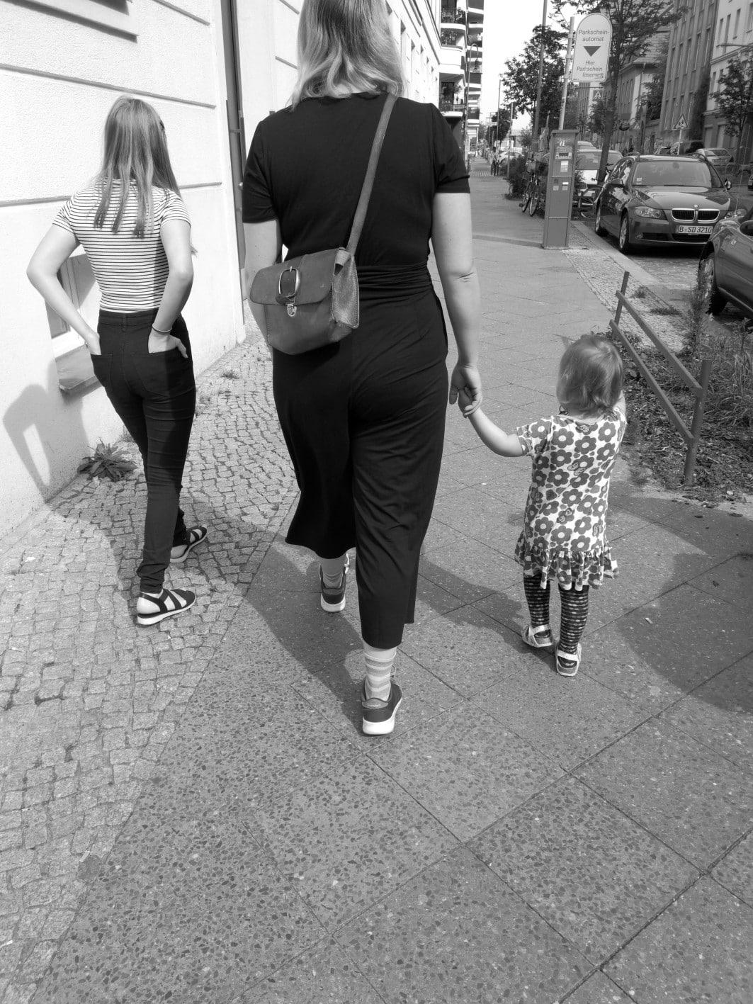 Frau mit zwei Kindern an der Hand