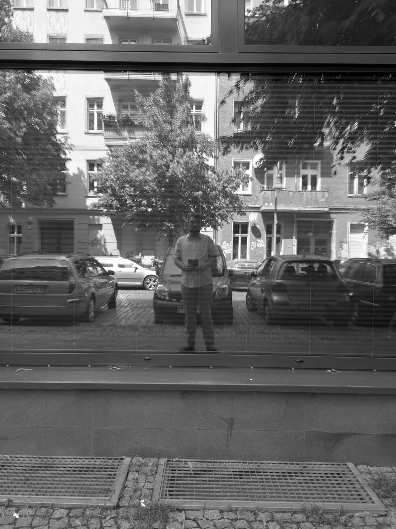 Mann vor einer Glasscheibe im Spiegel