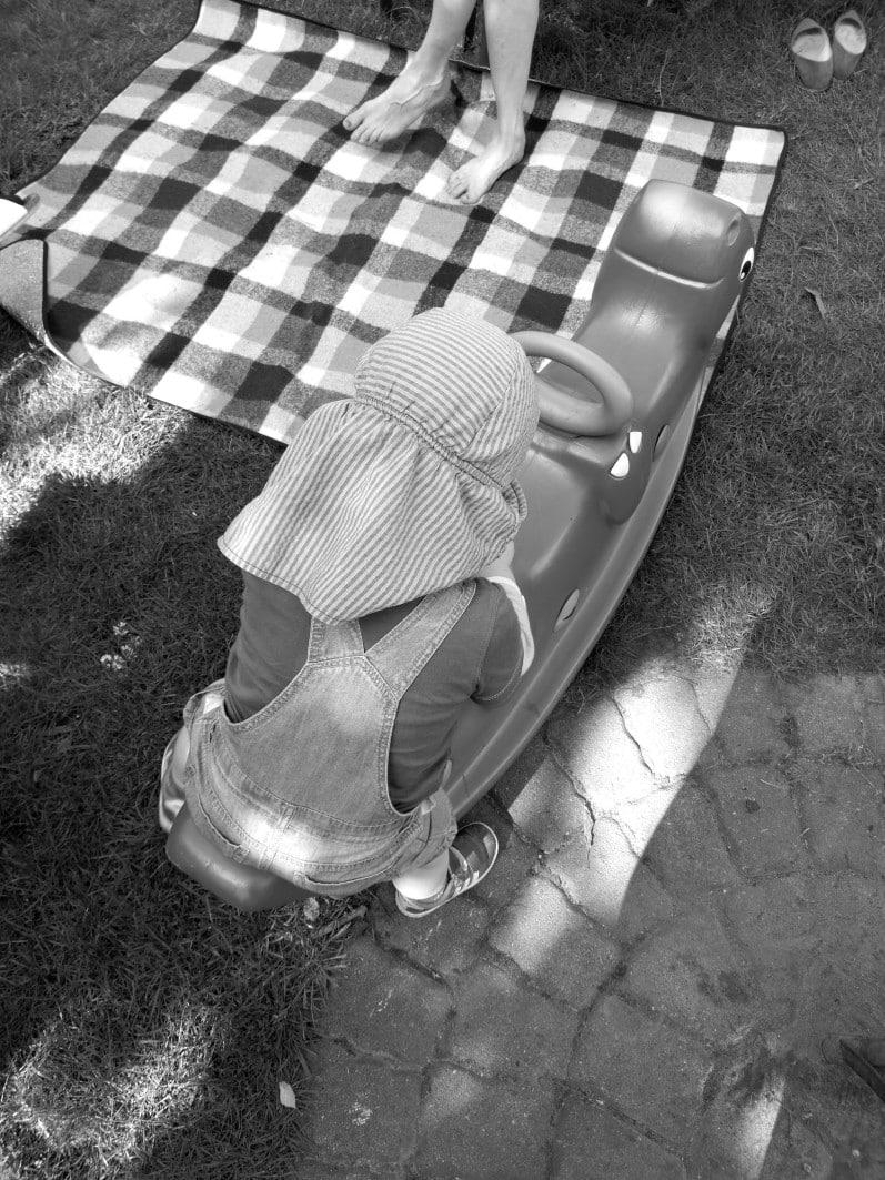 Kind auf einer Wippe, karierte Decke