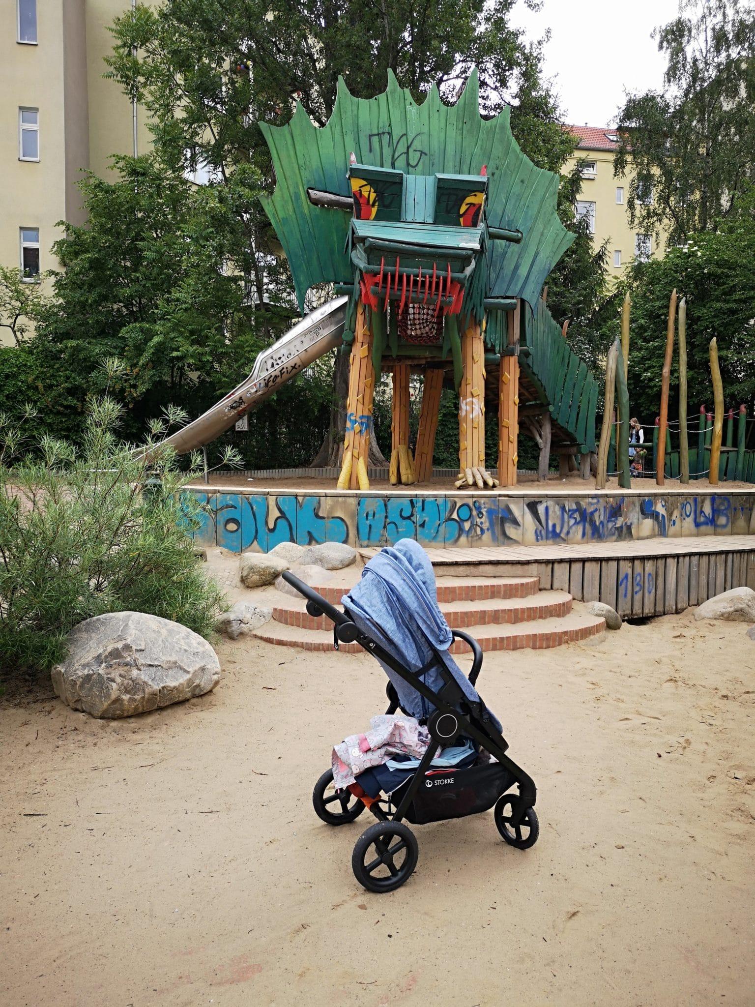 ein Kinderwagen auf einem Spielplatz mit einem Drachenkopf