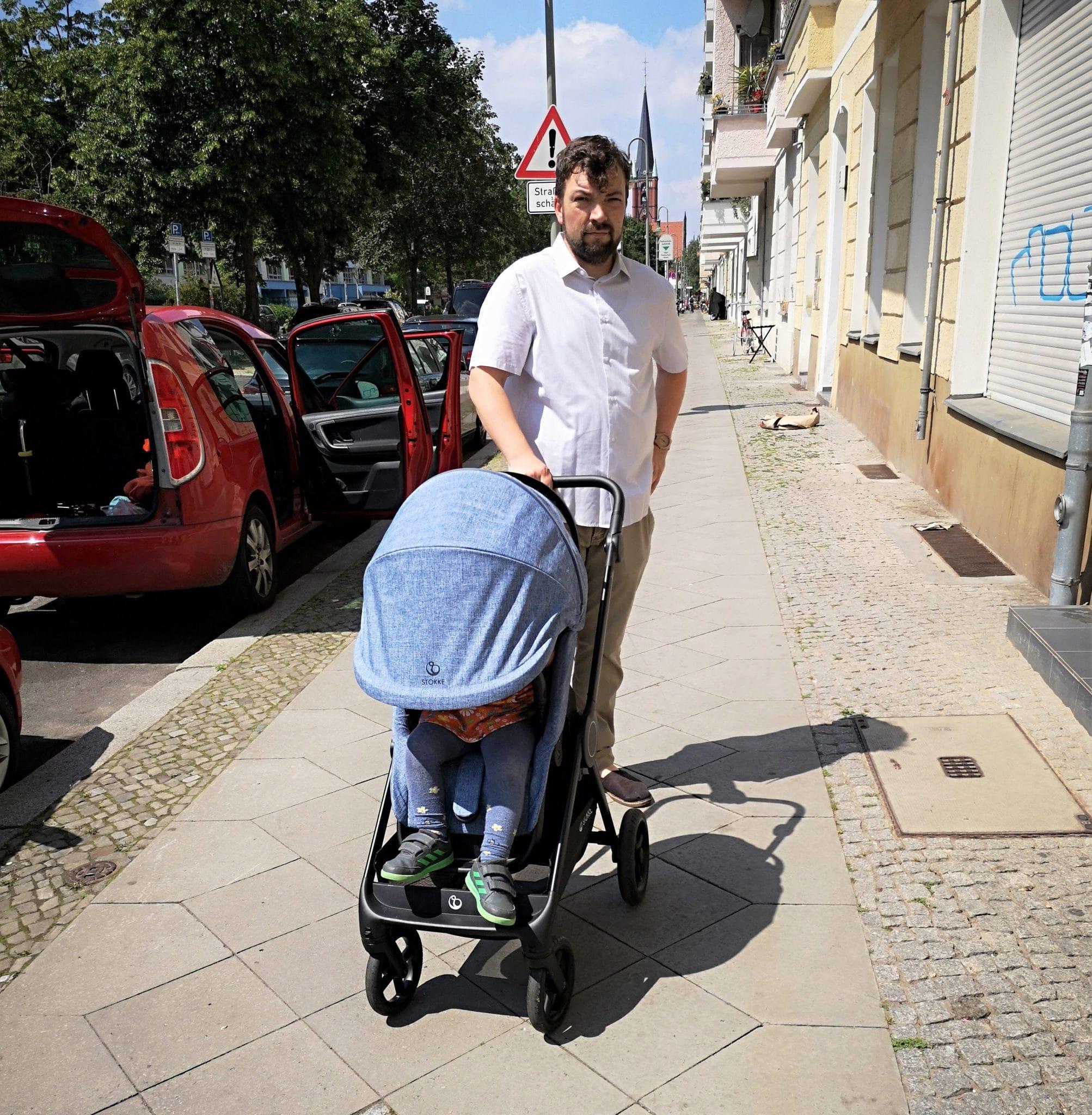Ein Mann schiebt einen Kinderwagen in hellem blau
