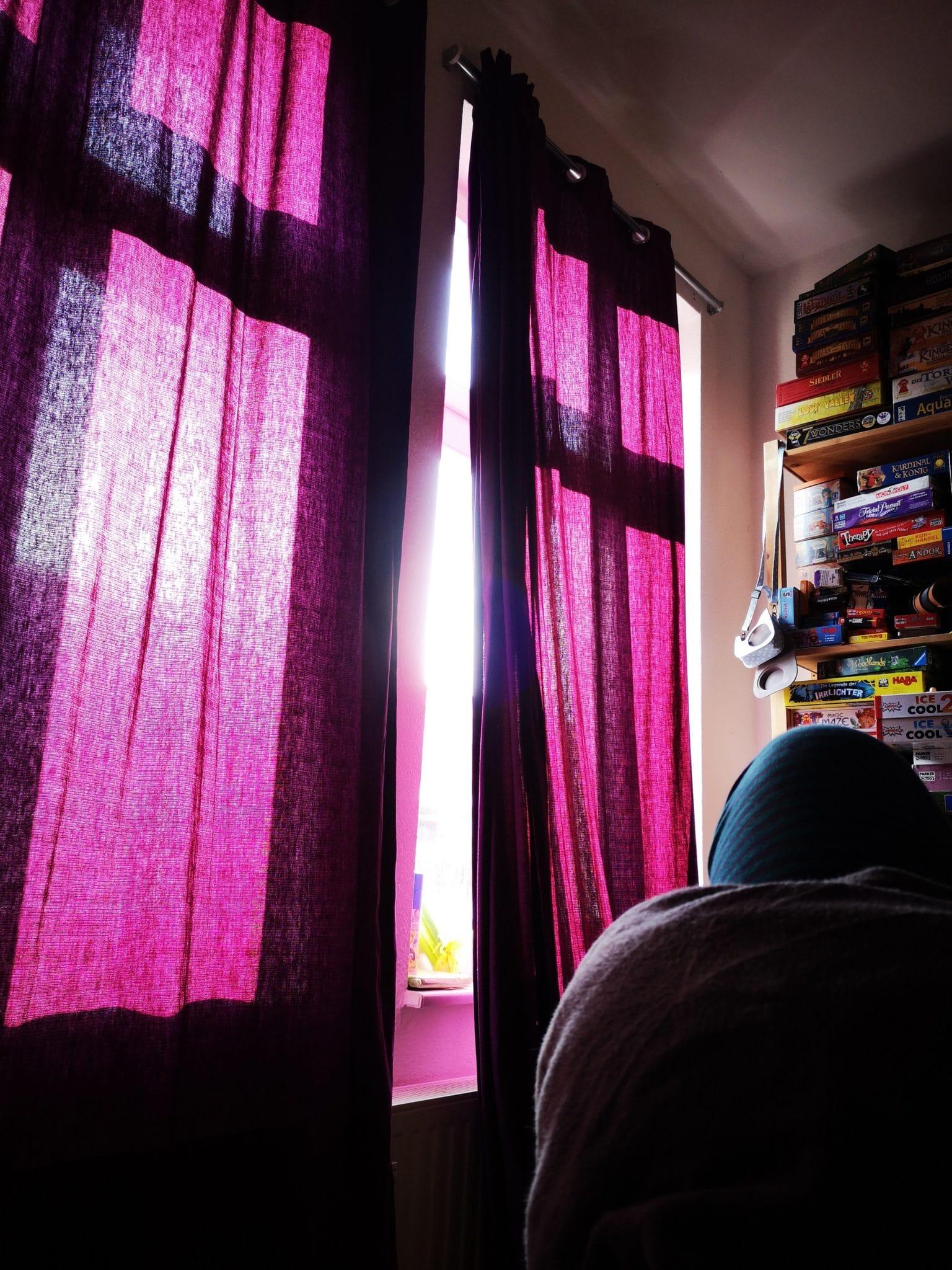 lila vorhänge, das Licht fällt in ein Zimmer hinein