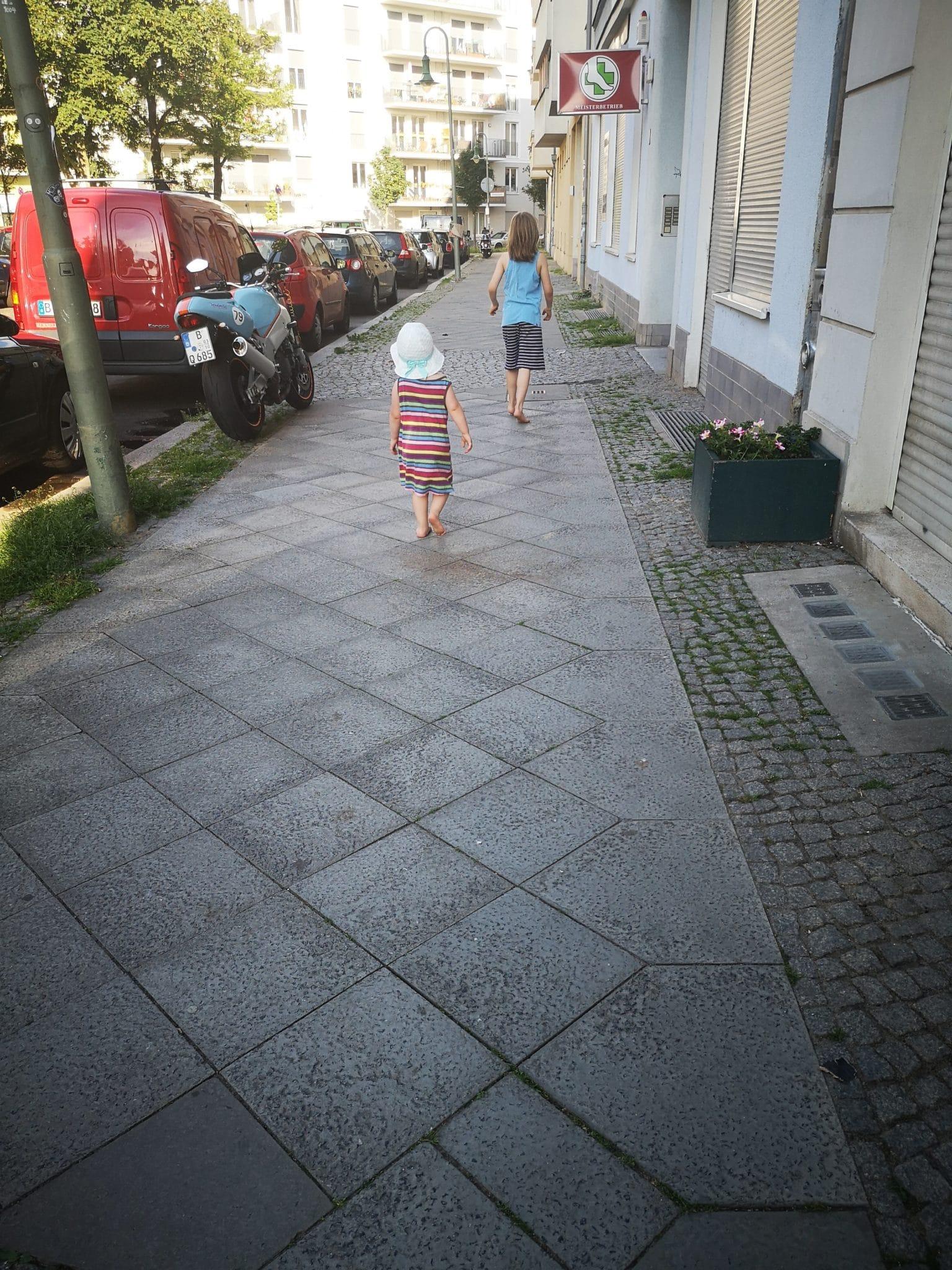 Zwei Kinder laufen barfuss auf dem Gehweg.