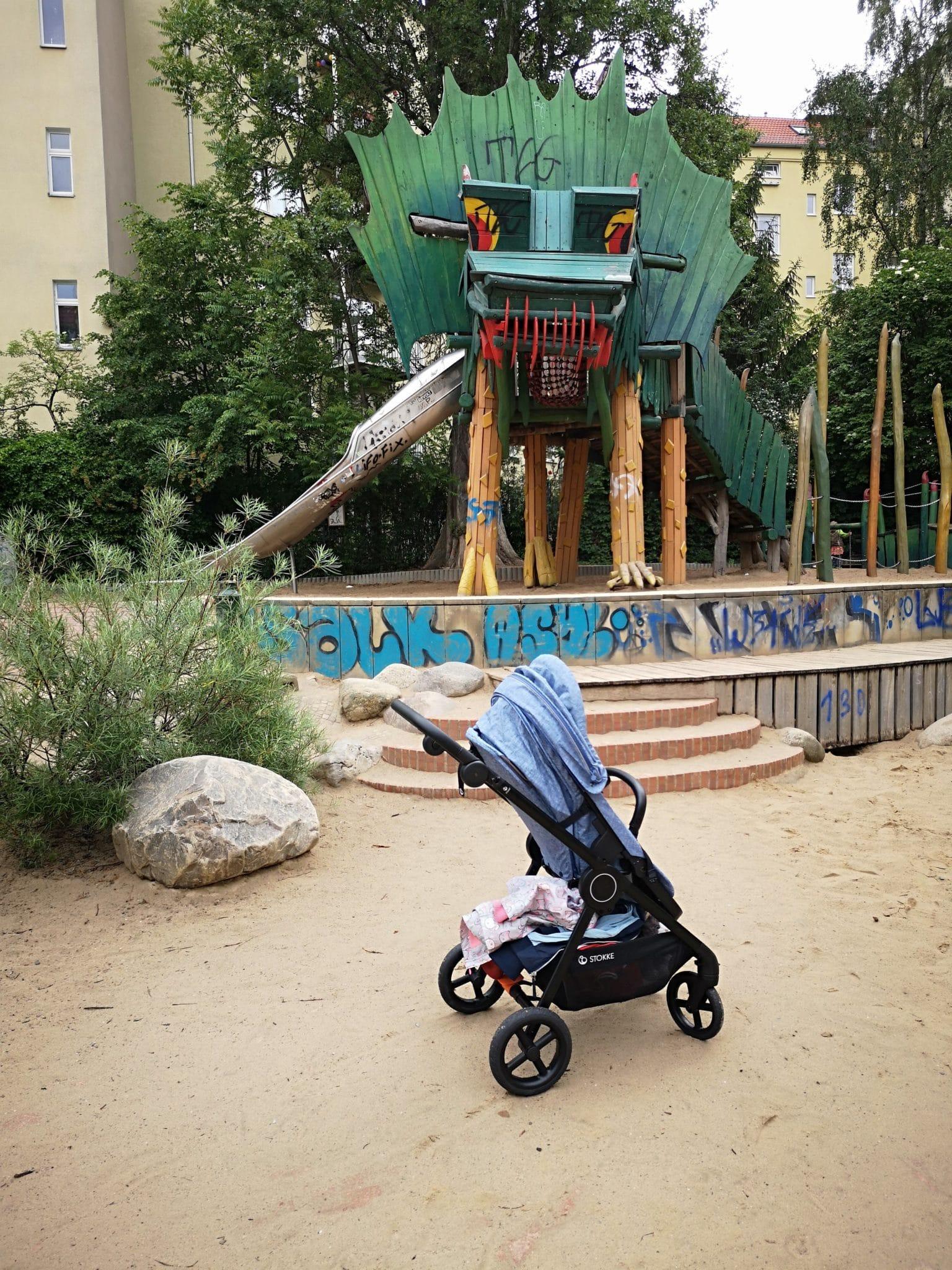 Ein Kinderwagen auf einem Spielplatz im Hintergrund ein Drachenkopf