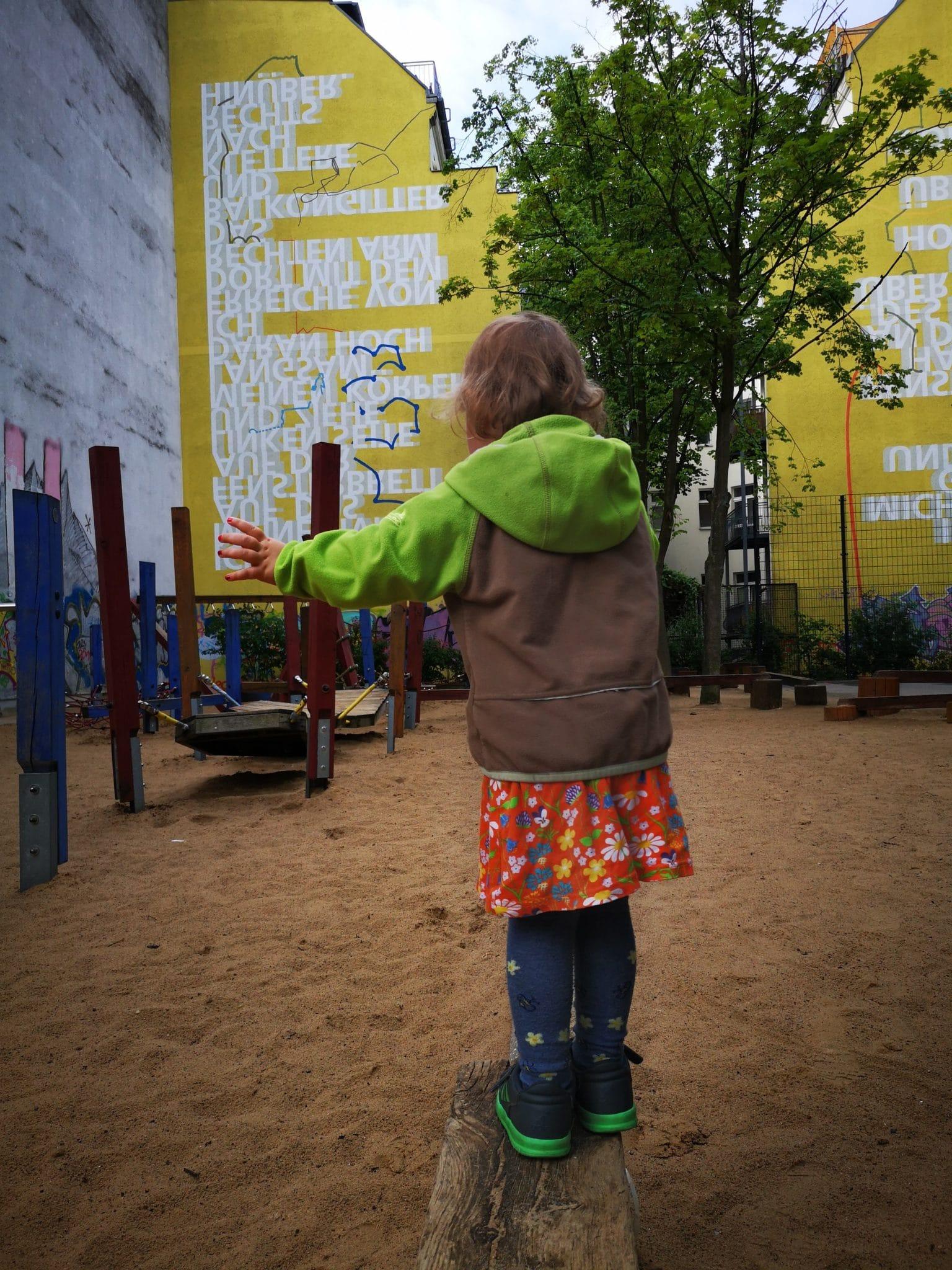 Ein Kleinkind balanciert auf einem Spielplatz.