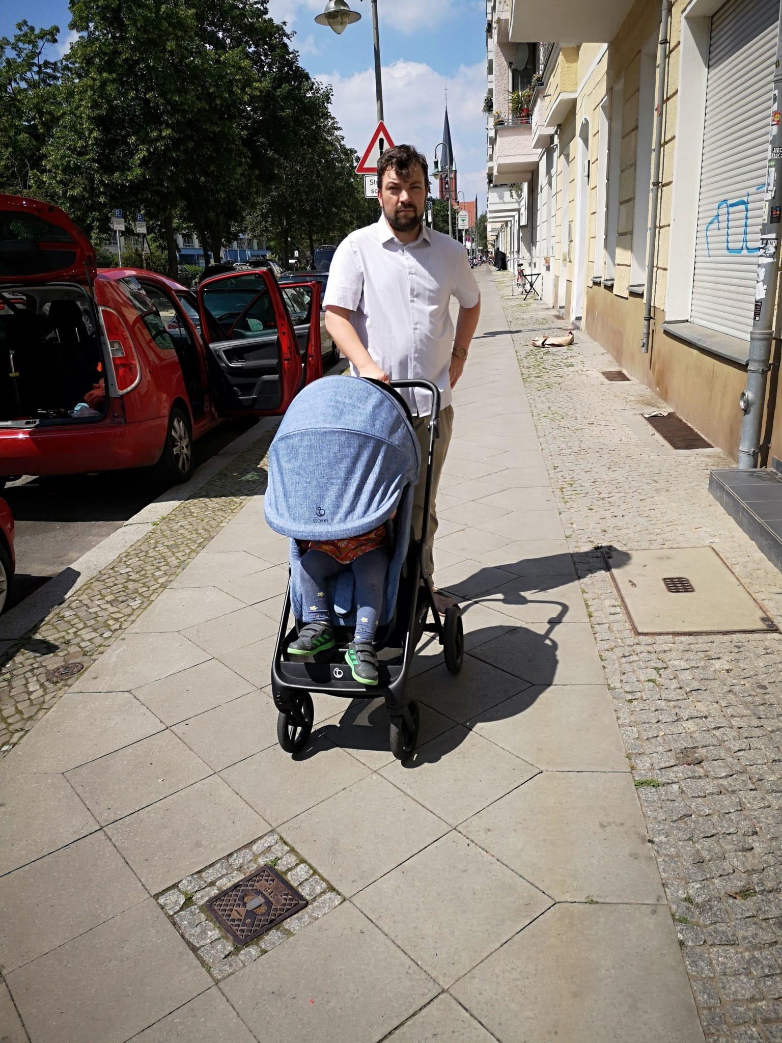 Ein Mann schiebt einen Kinderwagen auf einer Straße