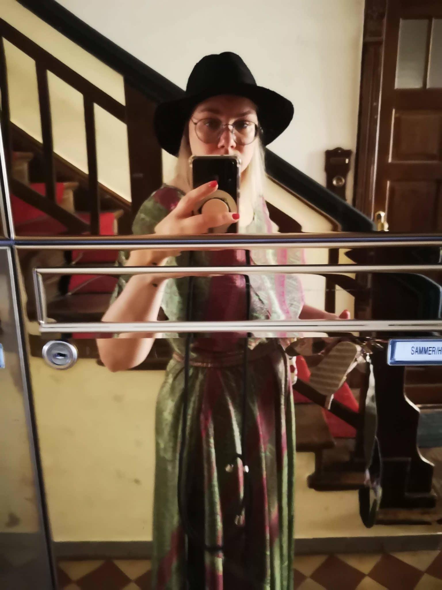 Frau in Kleid vor einem Briefkasten