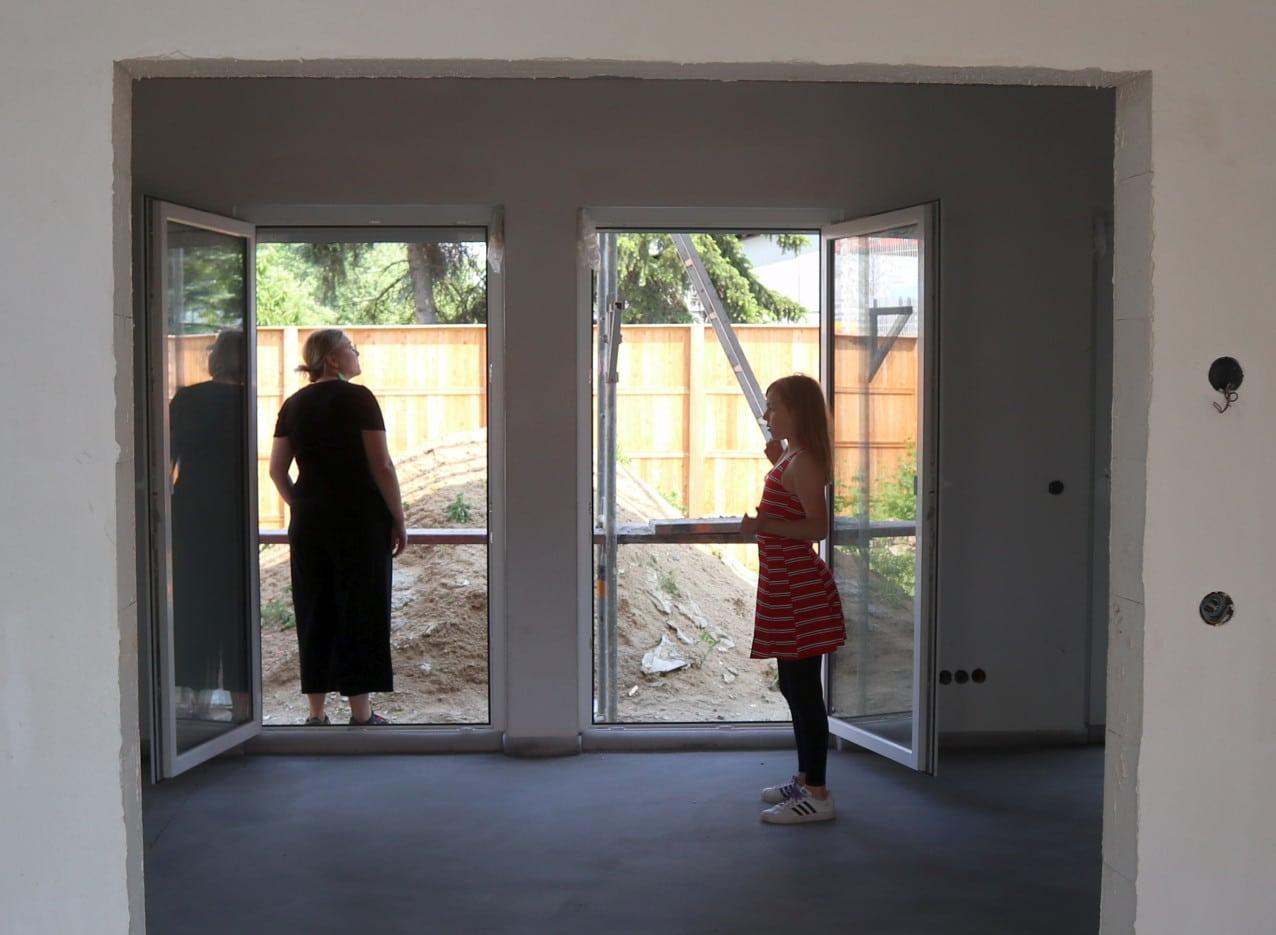 Eine Frau und ein Kind stehen vor einer offenen Balkontür