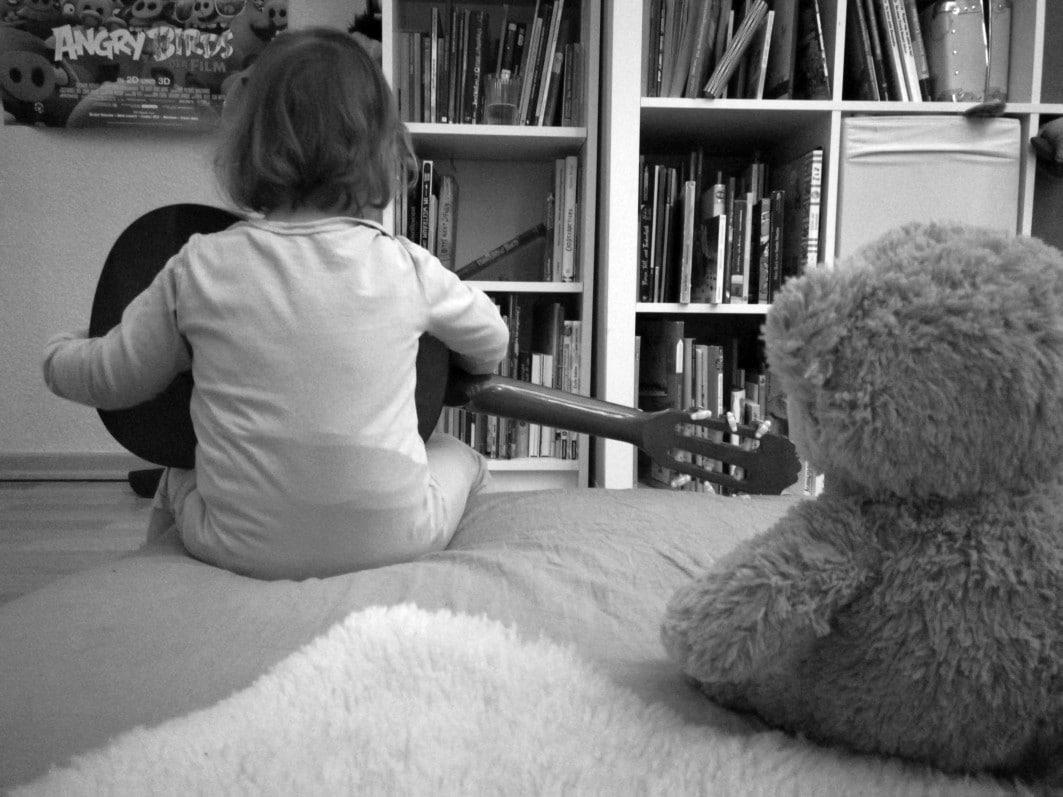 Ein Kind auf dem Bett spielt Gitarre