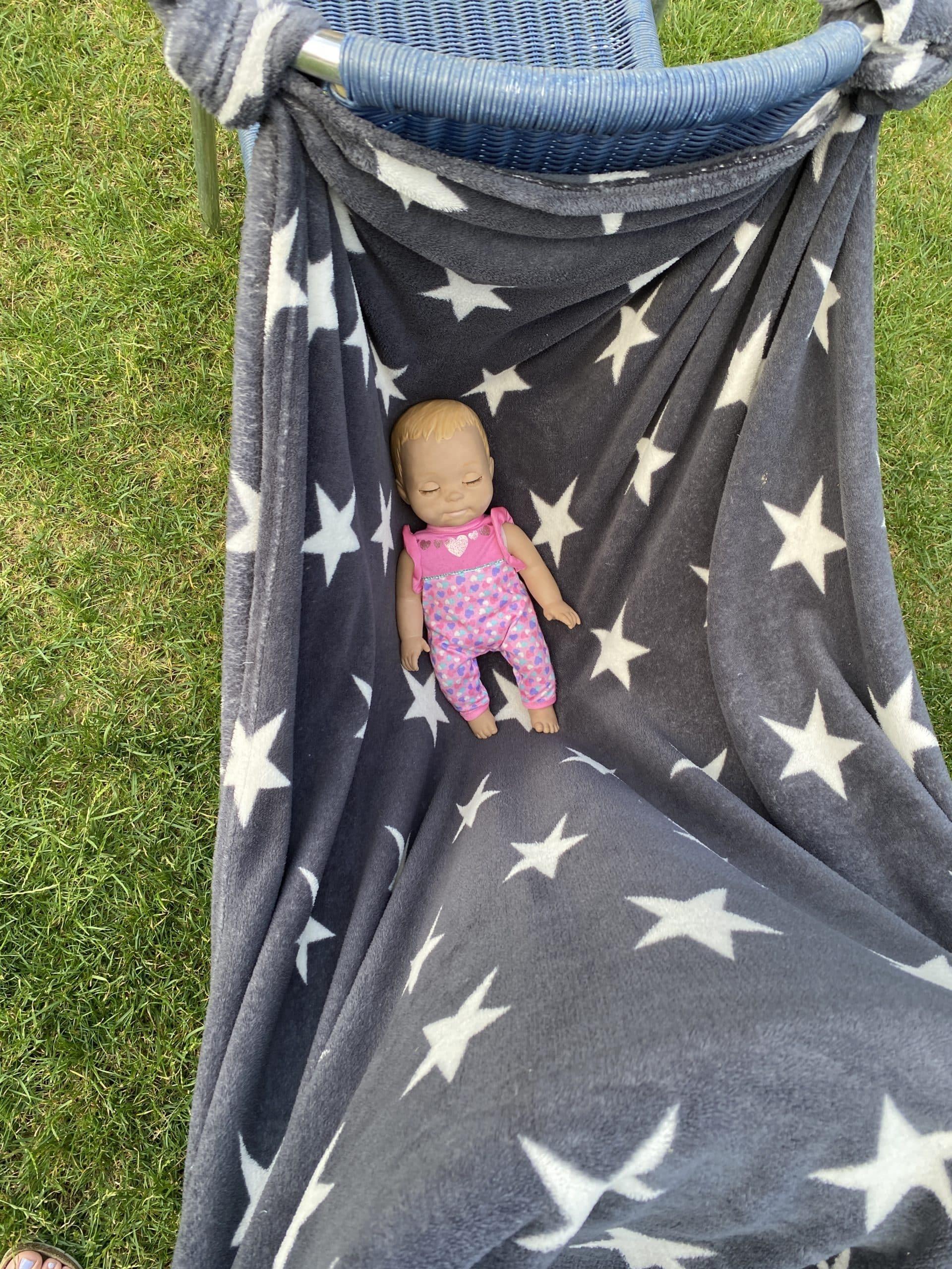 Im Garten sind die Kinder mit Puppenbetten beschäftigt.